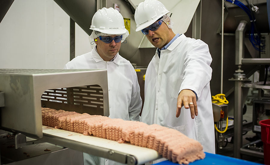 Andy Hanacek and Frank Koekkoek Jr., complex manager for Raeford, talk about the startup of the ground turkey tray-pack line running during Hanacek's visit to the new facility in mid-November