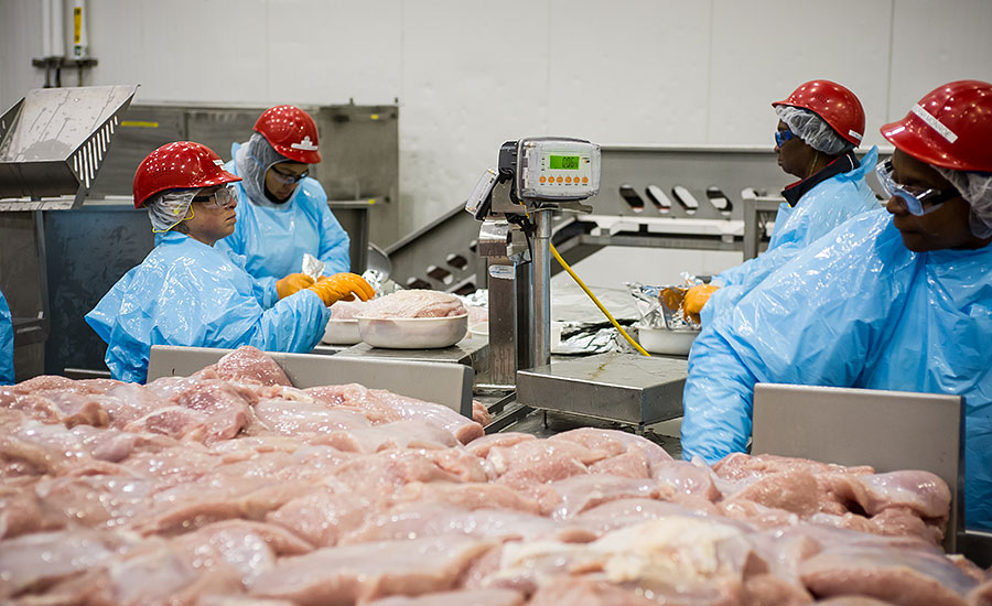 Butterball's Raeford plant employees pack raw roast products into trays