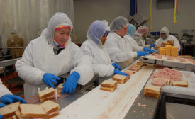 AdvancePierre Foods employees assemble legacy Landshire-branded wedge sandwiches and line them up to be sliced