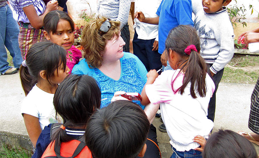 A Hormel Foods employee sits with Guatemalan children