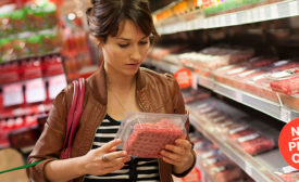 Woman Reading Ingredients on Food Label for Meat Product
