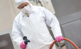 Meat/Poultry Plant Worker Sanitizes Equipment with Chemicals