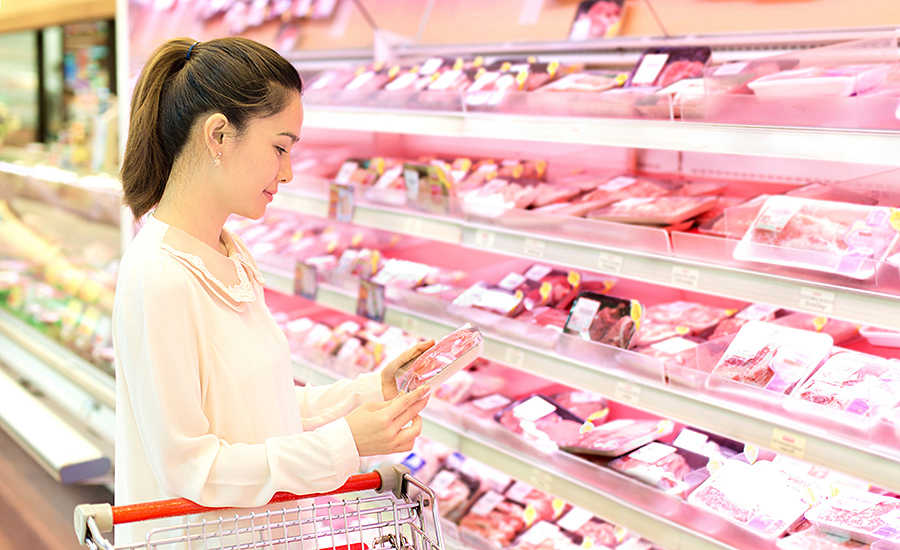 Woman Looking at Packaged Meat in Store
