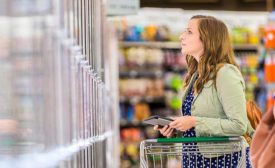 Woman Looking at Frozen Food in Grocery Aisle