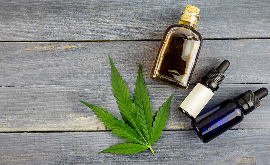 Marijuana Leaf and Bottles of CBD Oil