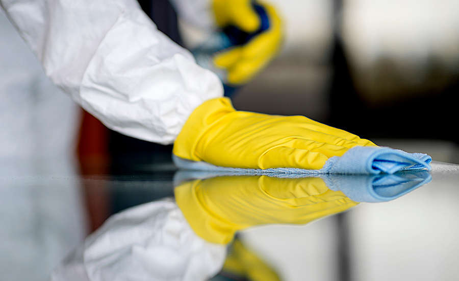 gloved hand wiping down a surface